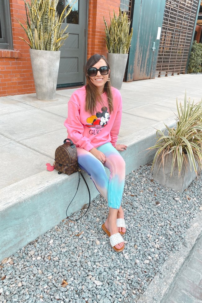 pink gucci disney sweatshirt with tie die joggers and louis vuitton palm springs