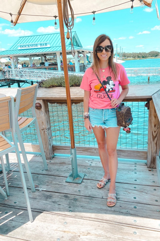pink gucci disney tee with agolde shorts and louis vuitton palm springs mini