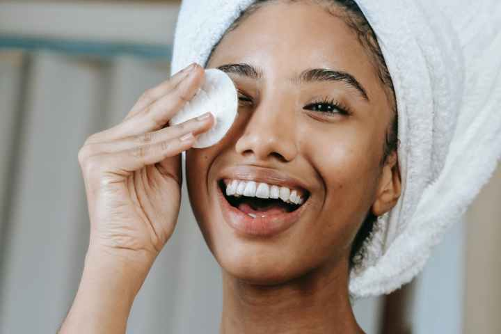 ethnic smiling woman wiping face with cotton pad