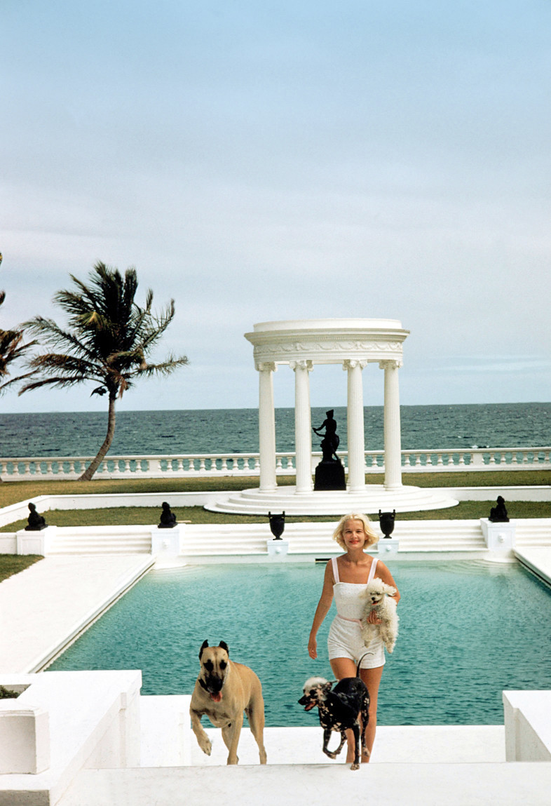 Premium Rates Apply. circa 1955:  Mrs F C Winston Guest (1920 - 2003) (aka Cee Zee Guest) with her dogs in front of the Grecian temple pool on her ocean-front estate, Villa Artemis, Palm Beach, Florida.  (Photo by Slim Aarons/Getty Images)
