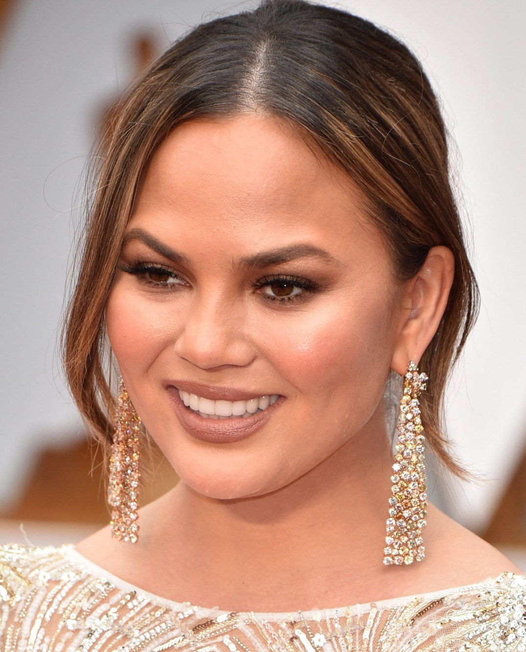 Chrissy Teigen Shimmers In Diamond Dangler Earrings By Lorraine Schwartz. PC- Harper's Bazaar
