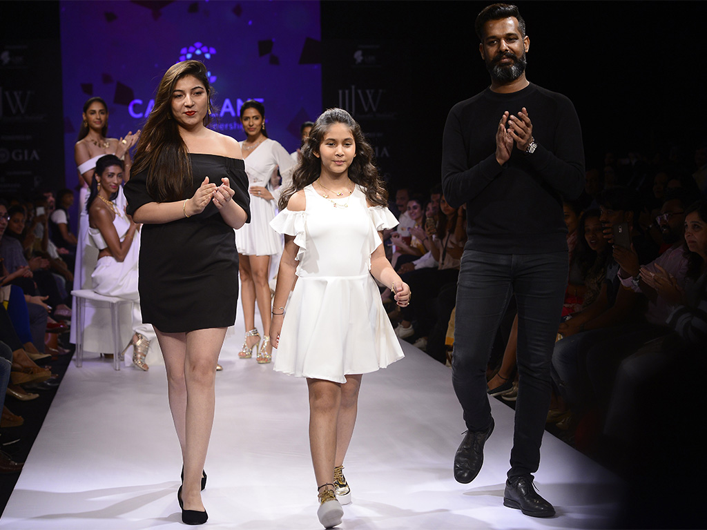 Caratlane Stole The Show With The Presence Of Little Miss Aarya Joshi Wearing The Wonderland Collection For Kids As She Confidently Walks With The Jewellery Designers Sumanpreet Kaur And Chetan Sharma. Caratlane Presented Their Everyday Wear And Gold Jewellery Collections At IIJW 2017. PC-YouTube