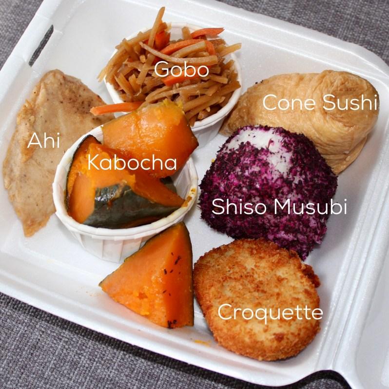 Fukuya plate with gobo, cone sushi, shiso musubi, croquette, kabocha, and ahi.