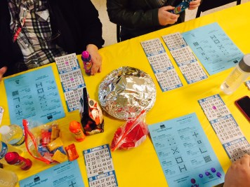 A table of four players is prepared with snacks before for the games begin. Each tests their dauber in the free spaces.