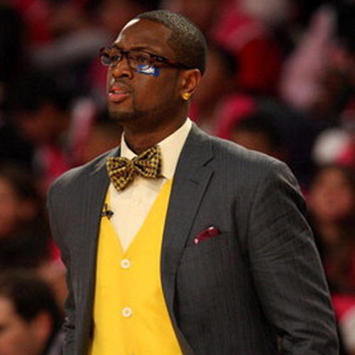 Dwayne Wade in a yellow checkered bowtie, yellow button down sweater and grey suit with glasses