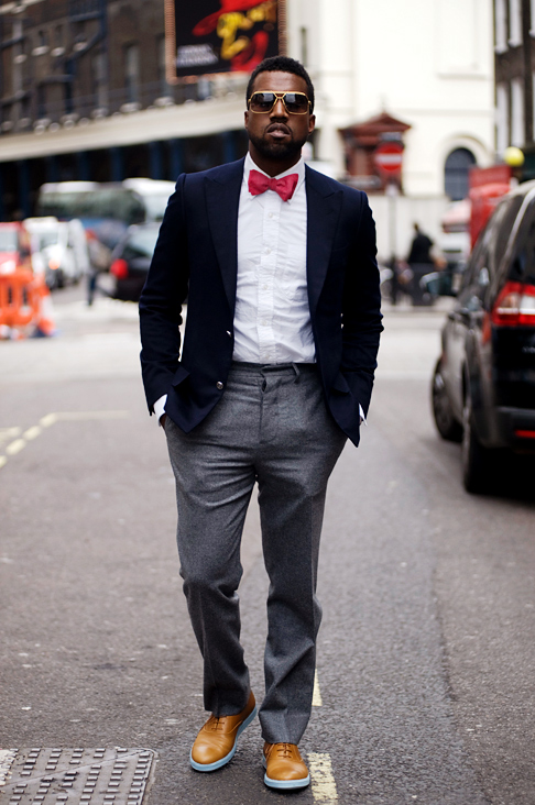 Kanye West in a cool, monotone look with a red bowtie which makes the outift