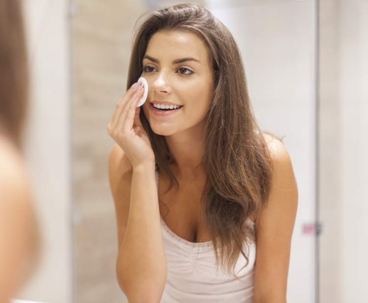 Beautiful brunette woman removing makeup from her face skincare toner
