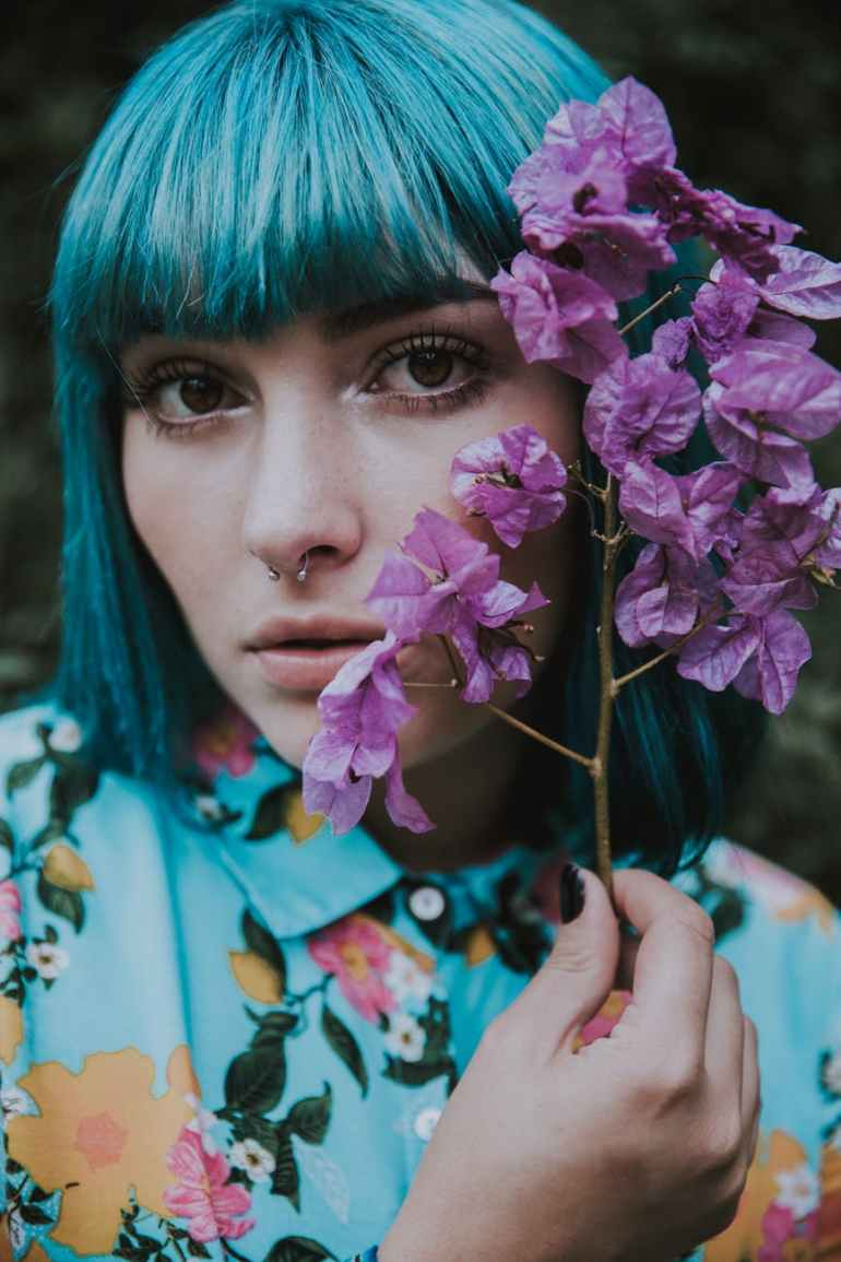 close up photo of woman holding flower