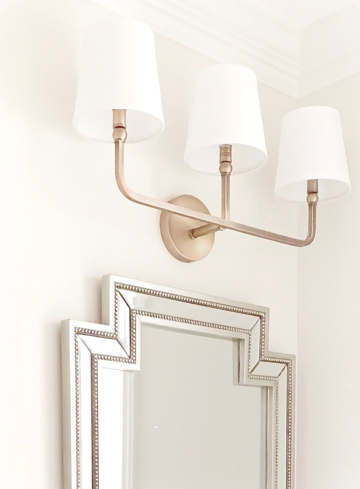 Styling Gypsy Interior Design traditional powder room featuring aged brass triple sconce light fixture and geometric silver beaded mirror. Walls painted Benjamin Moore Classic Gray.