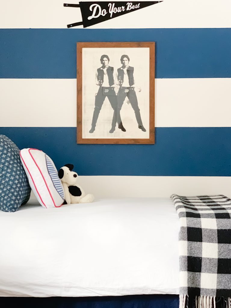 Styling Gypsy Interior Design | Classically Cool Boys Room reveal featuring a blue and white striped accent wall, iron bed, white bedding, newport cross pillow, letter block pillow, black plaid throw blanket, star wars art prints #boysroom #boysroomideas #boysroominspiration #starwarsbedroom #boysroomdecor #kidsroom