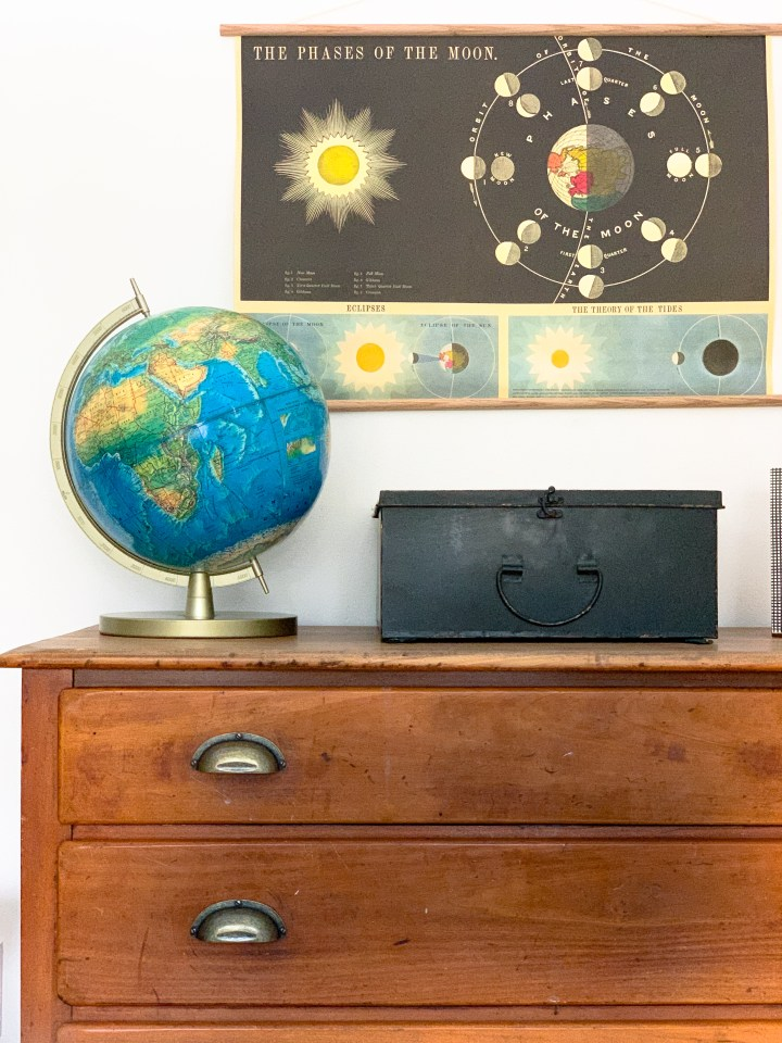 Styling Gypsy Interior Design | Classically Cool Boys Room reveal. Vignette features a vintage wood dresser with aged brass pulls, vintage globe, moon chart art print and vintage look black first aid box #boysroom #boysroomideas #boysroominspiration #starwarsbedroom #boysroomdecor #kidsroom