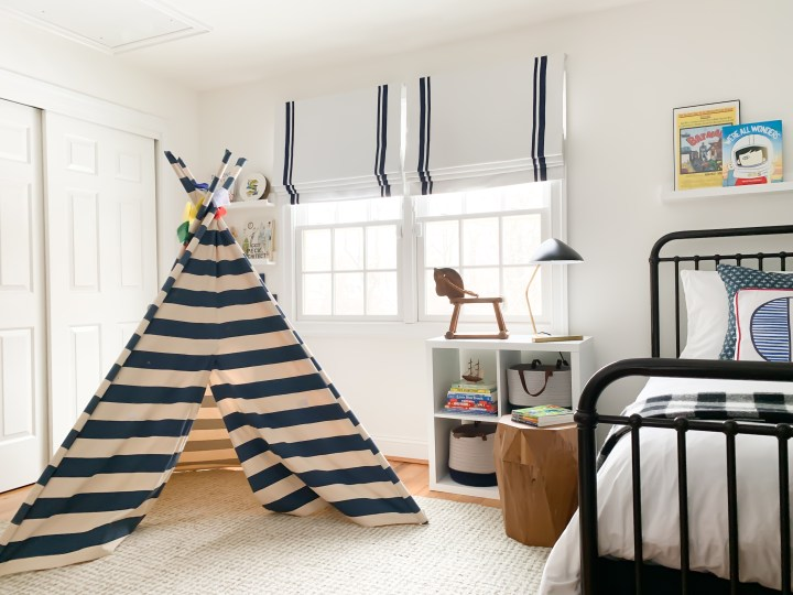 Styling Gypsy Interior Design | Classically Cool Boys Room reveal featuring an iron bed, blue and white striped teepee, roman shades, vintage rocking horse, mid-century table lamp, geometric wood stool, beige wool rug, star wars decor, navy blue storage baskets and ikea kallax shelves #boysroom #boysroomideas #boysroominspiration #starwarsbedroom #boysroomdecor #kidsroom