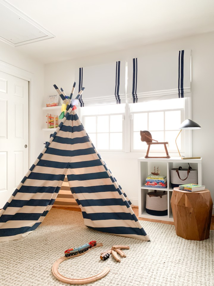 Styling Gypsy Interior Design | Classically Cool Boys Room reveal featuring a blue and white striped teepee, roman shades, vintage rocking horse, mid-century table lamp, geometric wood stool, beige wool rug, star wars decor, navy blue storage baskets and ikea kallax shelves #boysroom #boysroomideas #boysroominspiration #starwarsbedroom #boysroomdecor #kidsroom