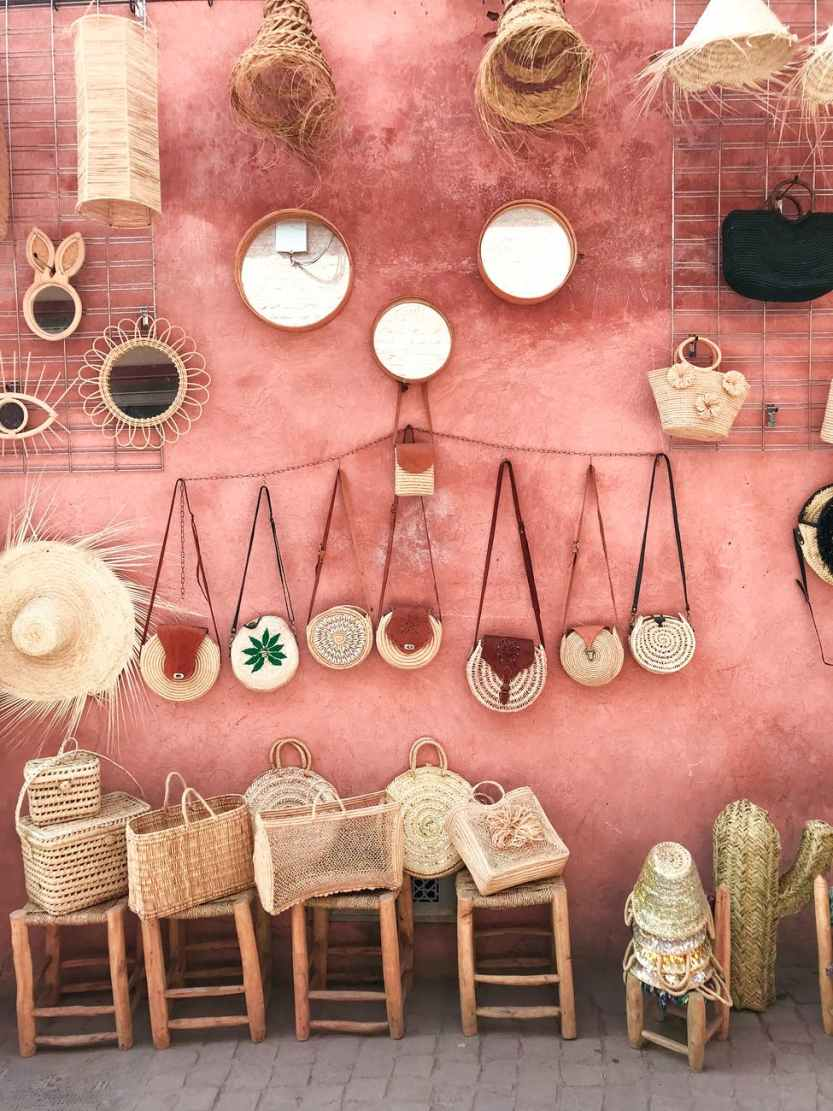photo of wicker bags and straw hats on a pink wall