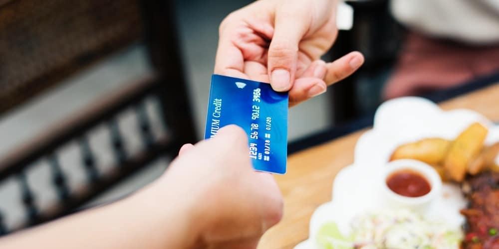 Uma pessoa entregando seu cartão de crédito para a outra, sugerindo que ela sabe como usar cartão de crédito.