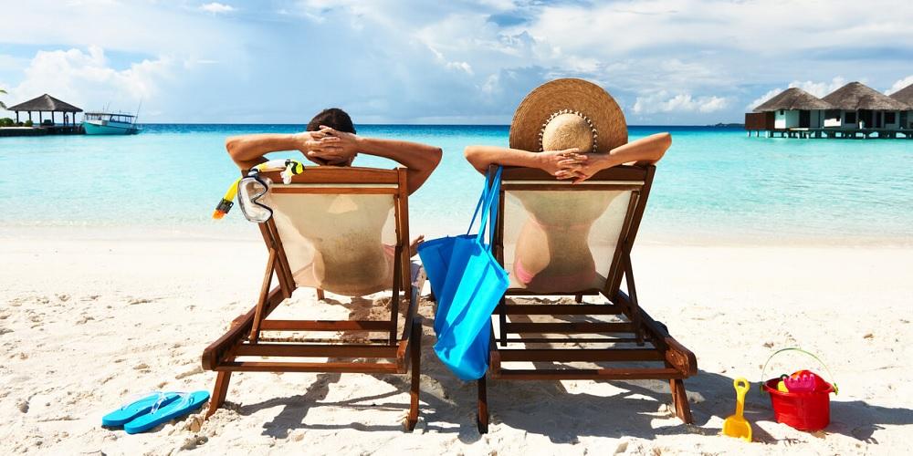 Casal sentado na beira da praia despreocupado do dinheiro porque já possui fontes de renda passiva.