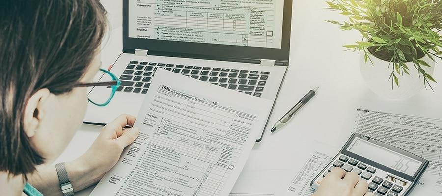 Mulher fazendo o pagamento de contas para manter organizada suas finanças pessoais.