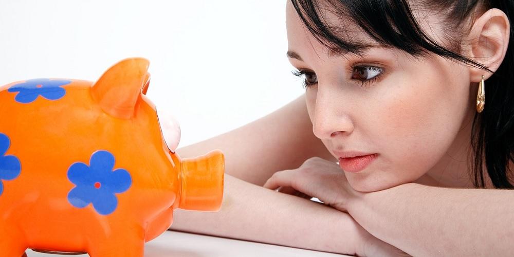 Mulher encarando seu cofrinho sem saber se já é o momento de começar a investir.