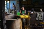 Seorang pekerja sedang mengangkat tahu yang sudah dikuningkan dengan cairan yang berasal dari rebusan kunyit. (Foto: Fajrul Islam/SJ)
