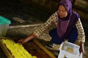 Seorang ibu sedang memindahkan tahu kuning ke dalam keranjang yang akan dibawanya keliling kampung. (Foto: Fajrul Islam/SJ)