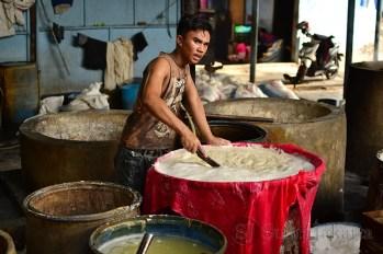 Arif sedang mengaduk kacang kedelai yang sudah dimasak dan disaring untuk diambil sarinya guna pembuatan tahu. (Foto: Fajrul Islam/SJ)