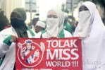 "Peserta aksi wanita memegang spanduk mini ""Tolak Miss World"". (Foto: Ujang Komar/SJ)"