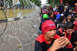 Para buruh duduk di depan Istana Negara dan dibatasi dengan kawat berduri. (Foto: Fajrul Islam/SJ)