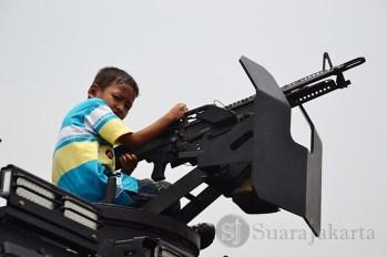 Seorang anak sedang memegang senjata yang ada di atas mobil tempur TNI. (Foto: Fajrul Islam)