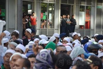 Calon penumpang busway menunggu sambil melihat aksi demonstrasi di depan Kedubes Australia (22/11) Kuningan, Jakarta. (Foto: Fajrul Islam)