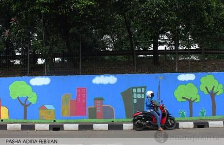 Pengendara sepeda motor berhenti di depan mural yang berada di Jalan M.H. Thamrin, Kota Tangerang. Senin (12/05/2014). (Foto: Pasha Aditia Febrian)