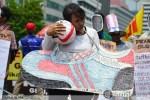 Buruh wanita membawa bola dan sepatu raksasa bermerek pada peringatan May Day di Jakarta (1/5). (Foto: Fajrul Islam)
