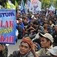 Seorang buruh memegang poster Tolak Upah Murah pada demo menolak kenaikan BBM di depan Istana Negara, Jakarta (10/12). (Foto: Fajrul Islam/SuaraJakarta)