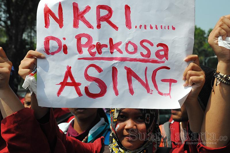 """Mahasiswi memegang poster """"NKRI Diperkosa Asing"""" pada Aksi Peringatan Harkitnas di Depan Istana Presiden, Jakarta Pusat (20/5). (Foto: Fajrul Islam/SuaraJakarta)"""