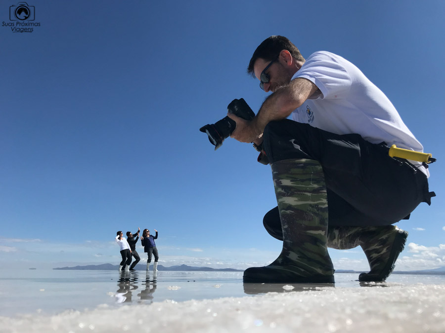 Imagem em perspectiva de um fotografo e pessoas distantes no salar de uyuni