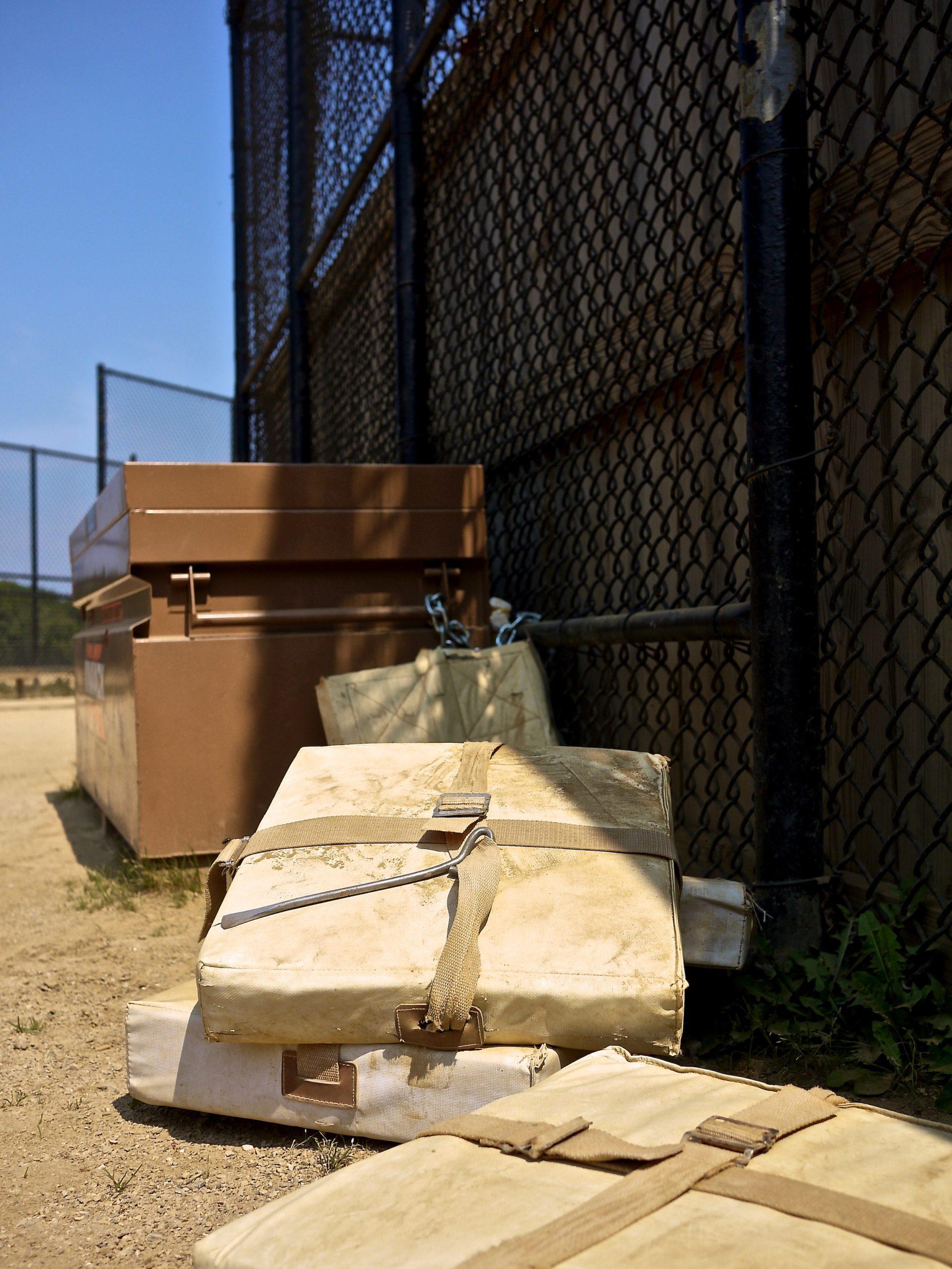 A pile of baseball bases sitting outside of a storage bin.
