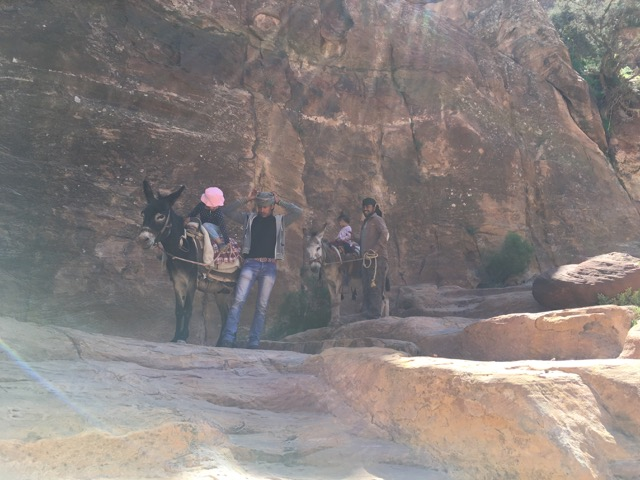 Travel with kids - The girls on donkeys and their guides in Petra