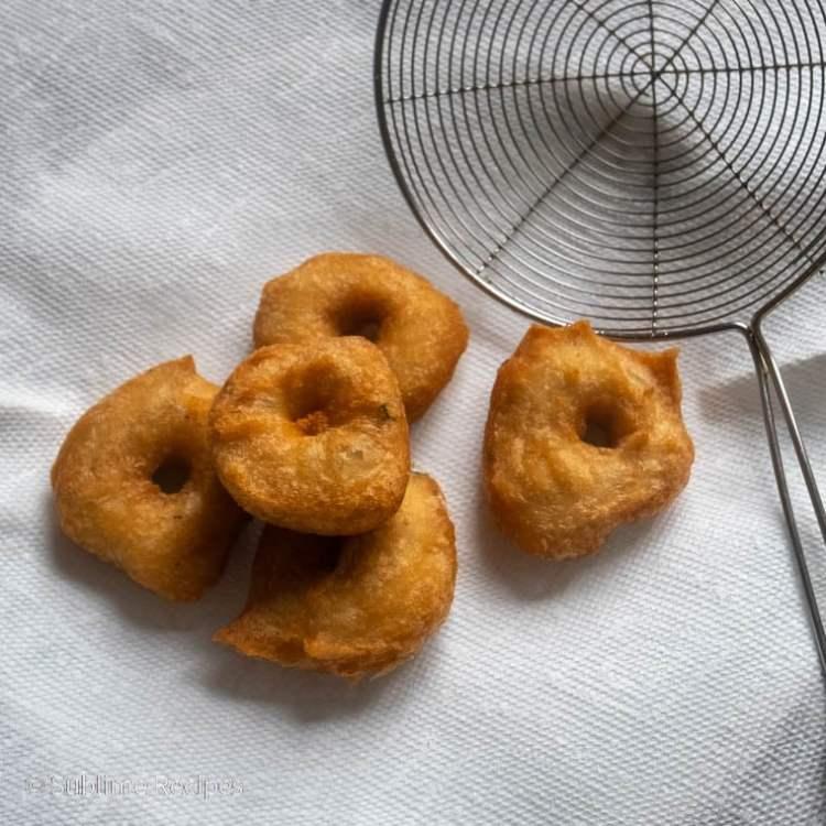Blotting fried medu vada on a kitchen paper towel