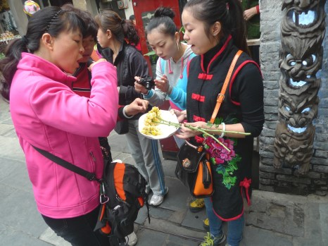 SHARING - Enjoying a snack of a fried blossom on a stem in Chengdu.