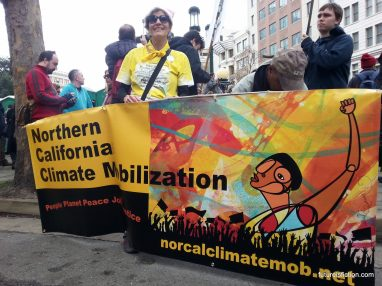 Oakland Women's March: woman holding climate mobilization banner