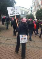 """back of protestor with booty flap reading """"Pussy Power"""" and a sign for disability rights: No Body Left Behind"""