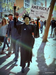 "woman dressed as the statue of liberty with sign"" ""America! You are smarter and better than this!"""