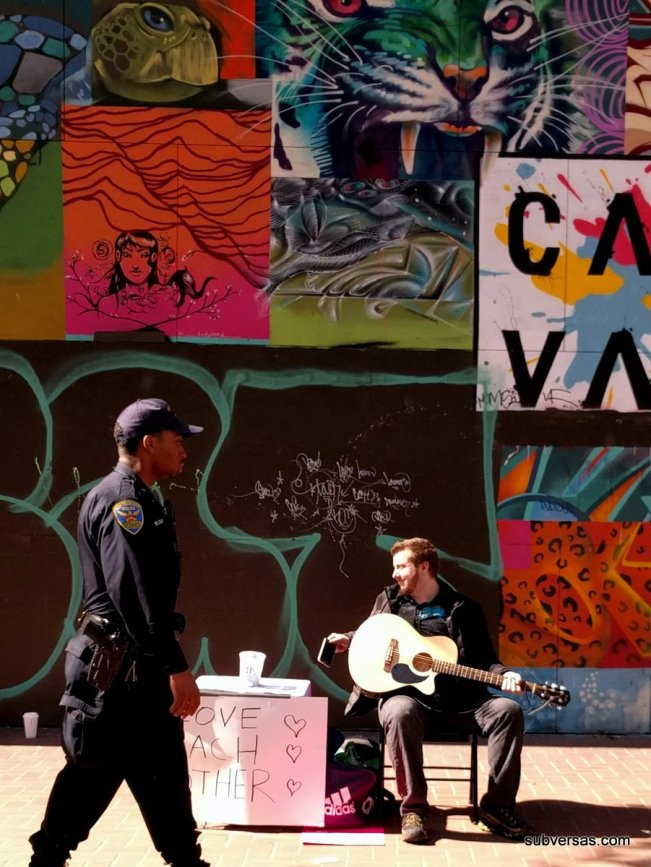 Man playing guitar takes a break, cop walks by, street art.