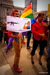 "Dude in heels with sign: ""Less of this [pic of gun] More of This [pic of Rosie the Riveter]"" standing next to guy in heels waving the rainbow flag."