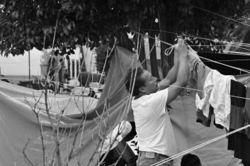 Un profesor improvisa un tendedero en uno de los lazos que sostienen las carpas del campamento. Fotografía: Martina Oliveiro