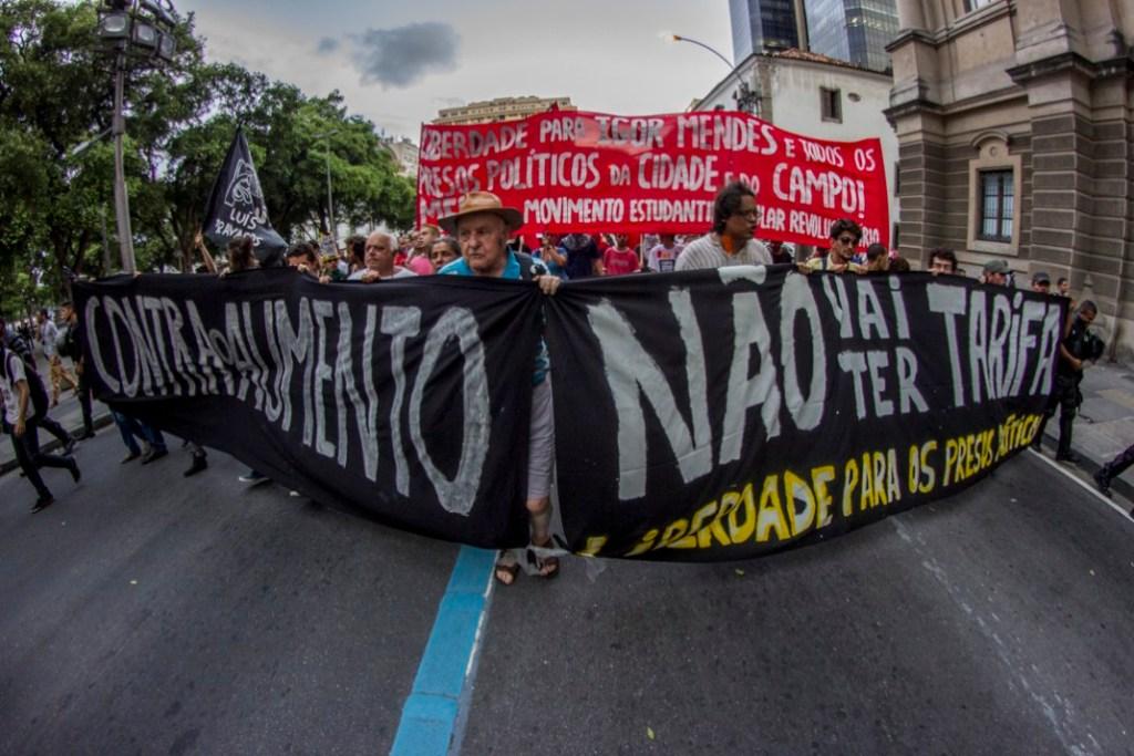 """23 de enero del 2015. Aspectos del cuarto acto contra el aumento a la tarifa del transporte público en la ciudad de Rio de Janeiro, Brasil. En esta ocasión medio millar de personas se dieron cita en las afueras del tribunal de justicia de la ciudad para sumar también la exigencia por la libertad de lxs presxs políticos y contra la criminalización de la protesta social. """"Queremos el fin de la policía militar"""" y """"Luchar no es un crimen"""" fueron las expresiones que más retumbaron durante el trayecto. En todo tiempo elementos policiacos (quienes doblaban el número de manifestantes) mantuvieron cercado el contingente, creando momentos de tensión al bloquear e impedir el paso de lxs manifestantes en diversas ocasiones quienes realizaron la protesta pacífica durante todo el tiempo. El contingente finalizó el acto en el mismo lugar del cual partió, no sin antes convocar mas movilizaciones para la siguiente semana. Fotografía: Aldo Santiago"""