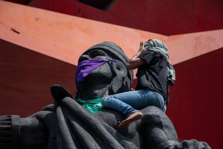 Mujeres escalan la estatua de Nezahualcóyotl en el Coyote Rojo para colocarle un paliacate morado y verde como símbolo de la lucha feminista en Neza. Al terminar de amarrarlos, todas la acompañamos con el grito de «Ni una más».