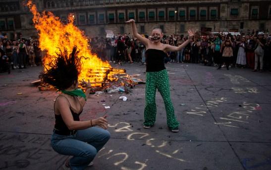 Dos mujeres abren la pista y comienzan a bailar alrededor de una gran fogata frente a Palacio Nacional.
