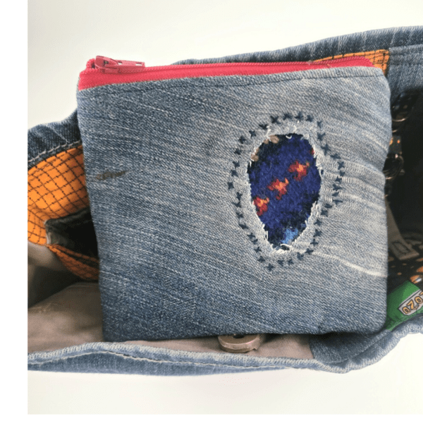 Upcycled tote view of zip pouch sitting on the top of the bag with visible mending feature