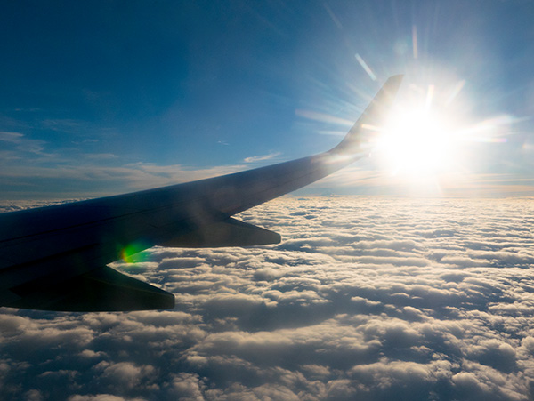 jet wing over clouds with sun