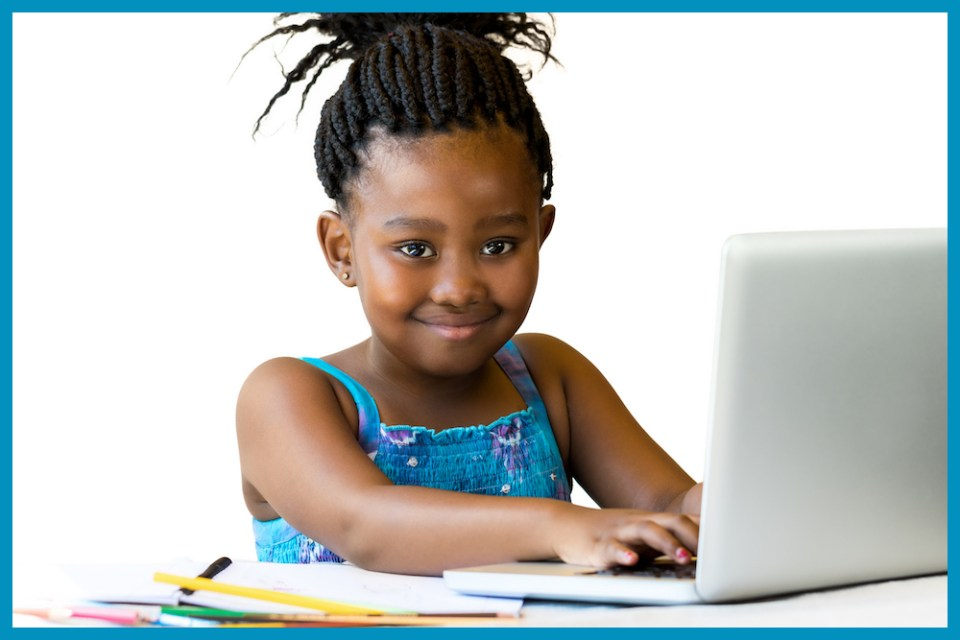 African youngster sitting with hands on keyboard.